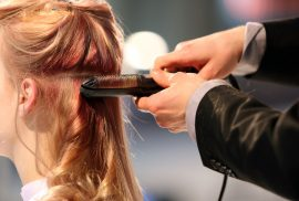Woman having hair curled by professional