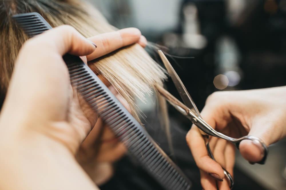 Woman having hair trimmed