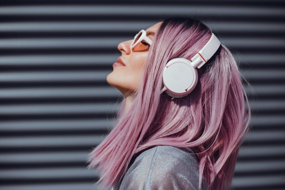 Woman with pink hair and headphones