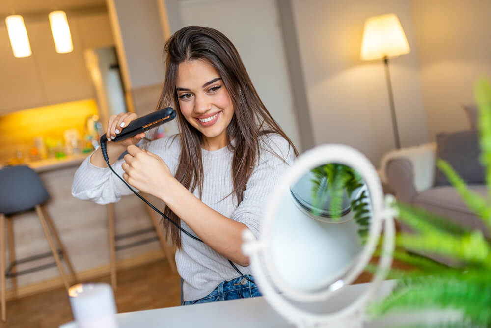 Woman using evolution straightener to straighten hair