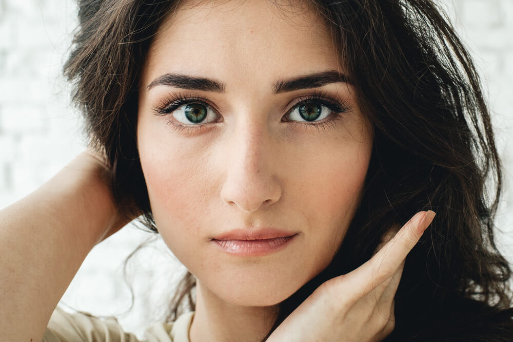 Woman with dark hair looking at camera