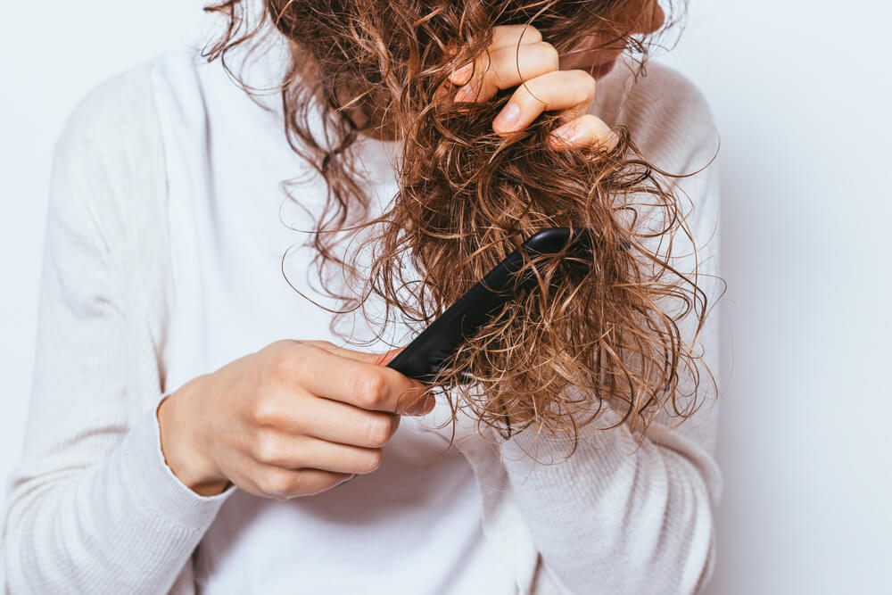 Woman combing tangled hair