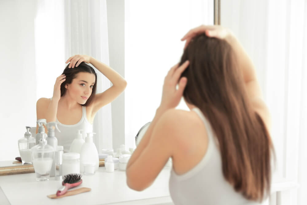 Woman looking at her hair in mirror
