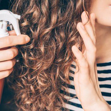 Woman spraying hair