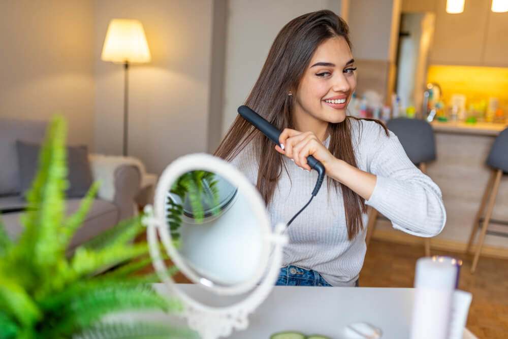 Woman straightening hair